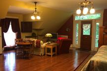 The living room space includes the dining room table and the big west window.