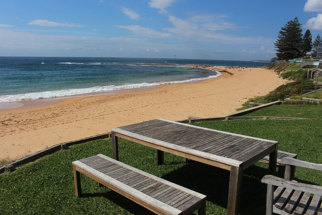 Communal picnic table and lawn looking towards rock pool