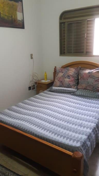 Cama de casal em madeira de lei em quarto bem arejado e com ventilador de teto.