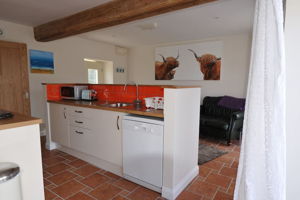 Open plan living/kitchen/diner. Electric hob and oven, dishwasher, microwave, toaster.