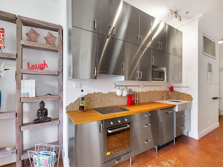 Brand new stainless steel kitchen with modern appliances including a dishwasher.