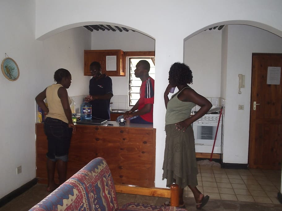 Open plan kitchen with previous guests preparing a meal.