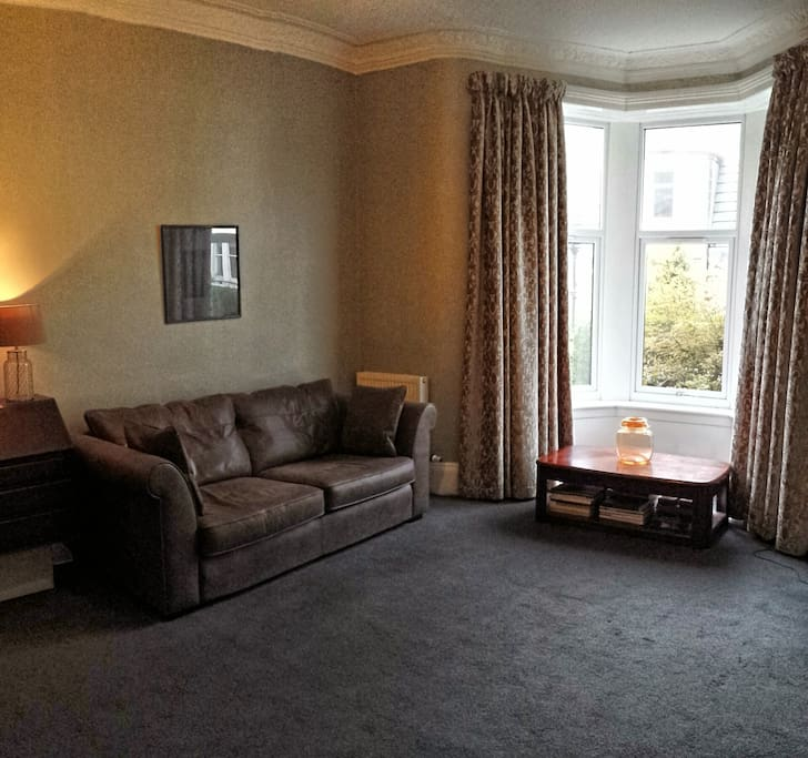 Spacious living room with bay window and large leather sofa.