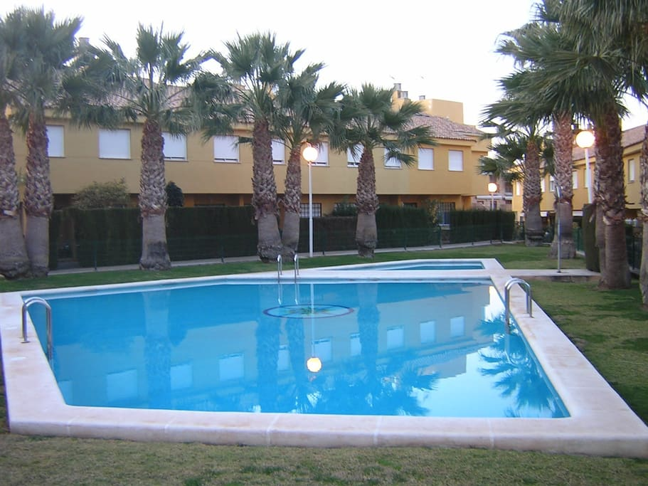 The swimming pool which is nearby the house.
