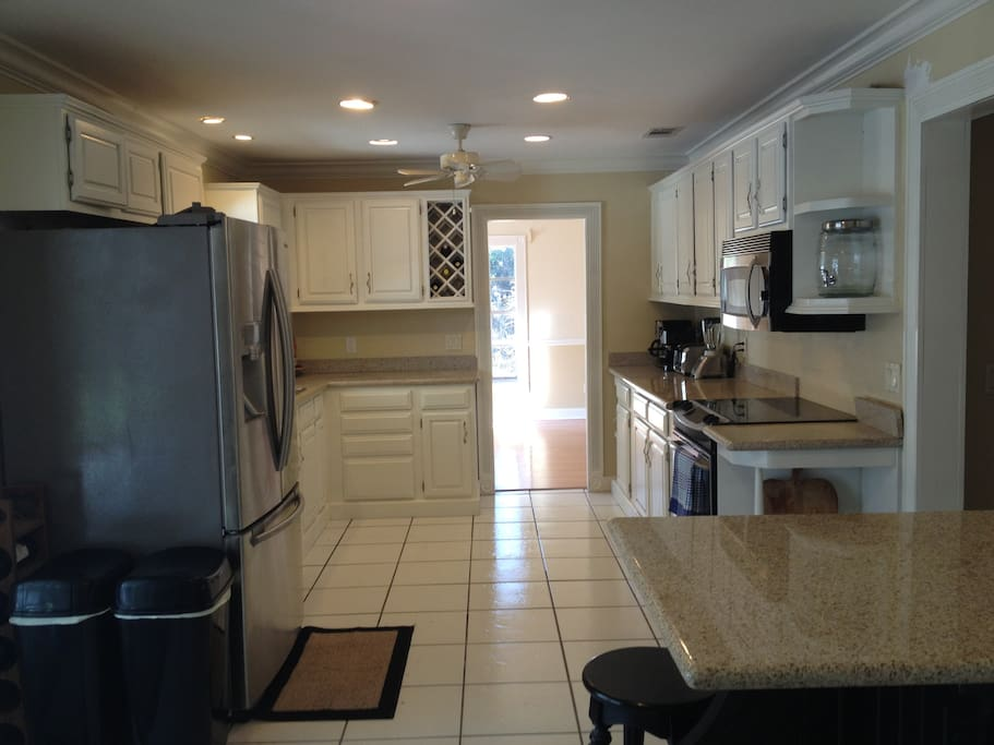 The modern all stainless kitchen with granite and huge frenchdoor fridge opens directly onto the lanai and pool