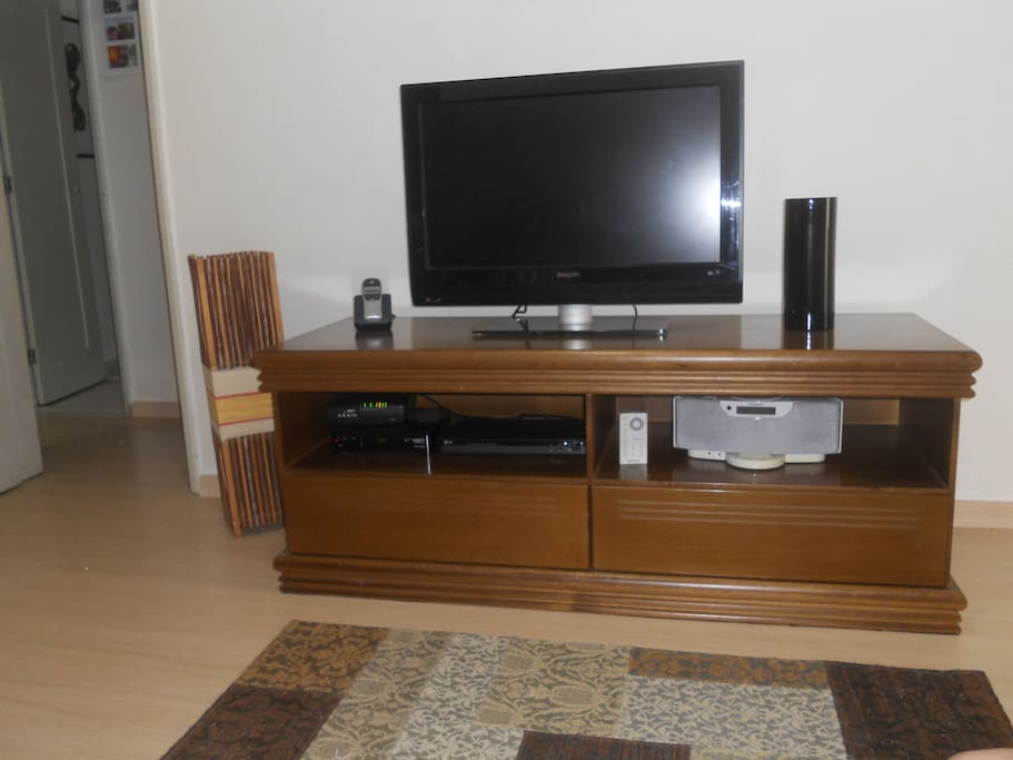 Sala de estar com TV de tela plana, DVD Player e canais a cabo.
