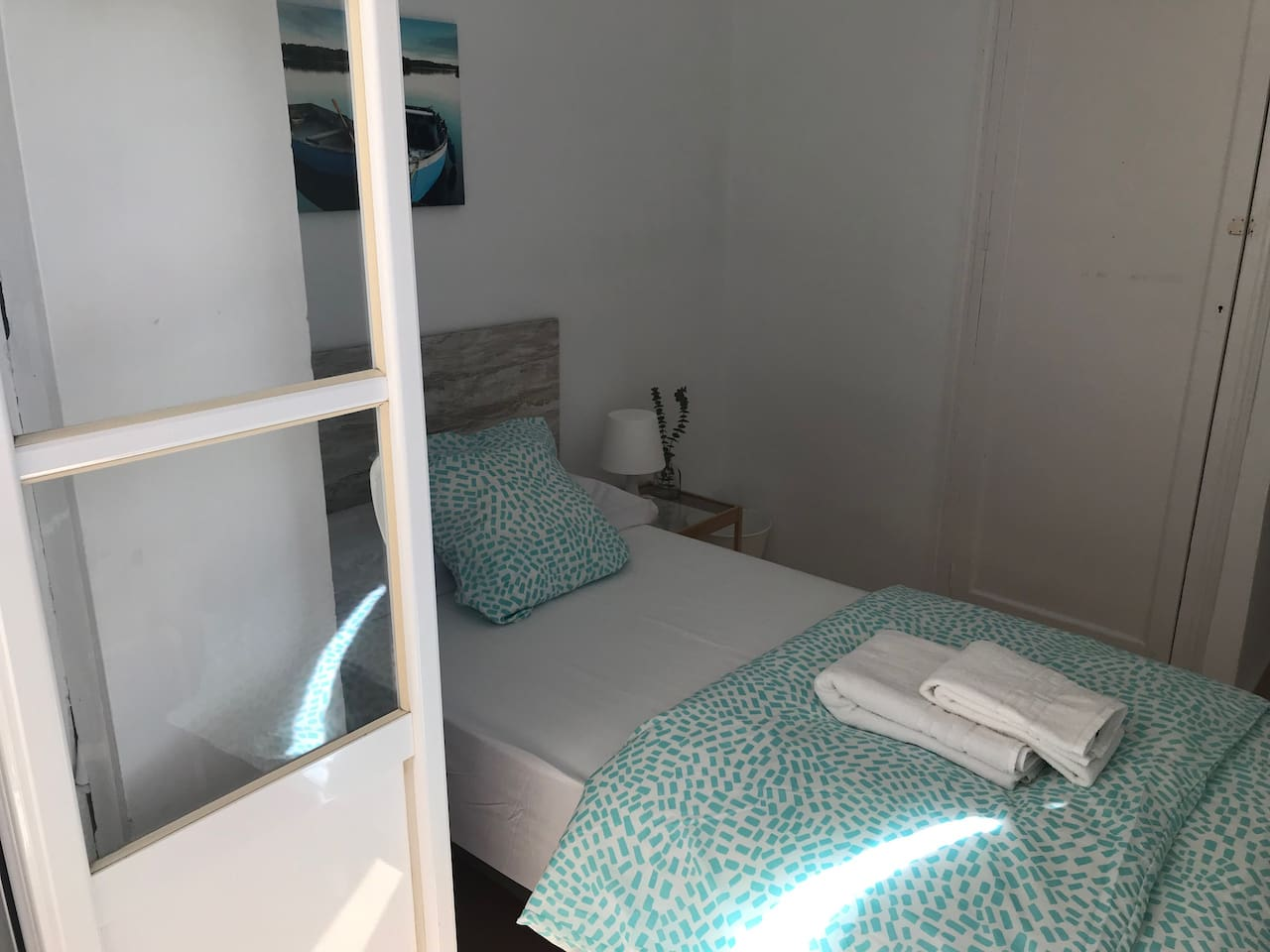 Habitación individual exterior con balcón a calle tranquila y luminosa. Dispone de armario, espejo y mobiliario básico. Conexión de wifi buena.