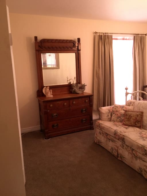 Antique dresser and mirror, a very comfortable loveseat rest on new luxurious   carpeting.