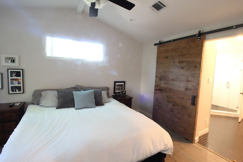 King bed master suite with wide opening through the barn door into the bathroom with a private toilet room and double vanity.
