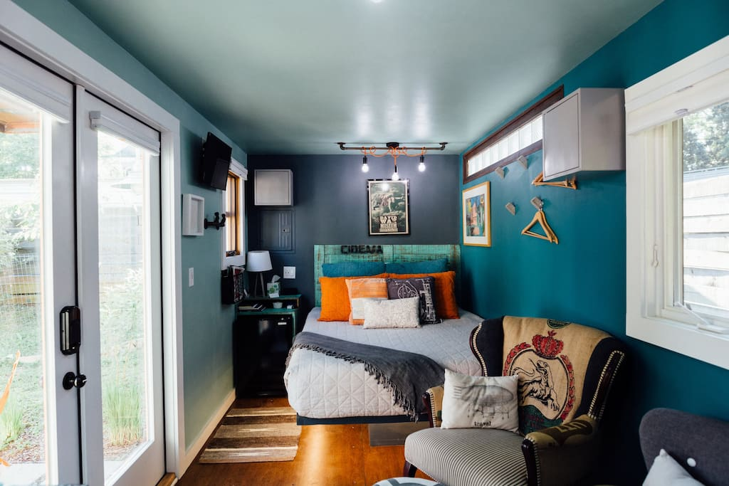 Headboard and nightstand / cubbies built from repurposed wood from Brazilian pallets, mini-fridge sits inside with storage cubbies around.