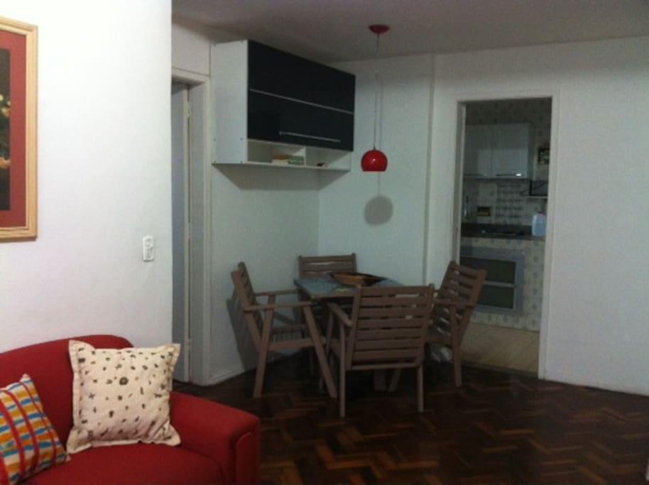Sala ampla, sofá, ventilador de teto, TV, mesa com 4 cadeiras
