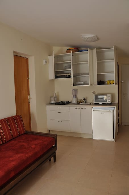 Kitchenette including Refrigerator, Microwave, two flames Gas stove and dishes.