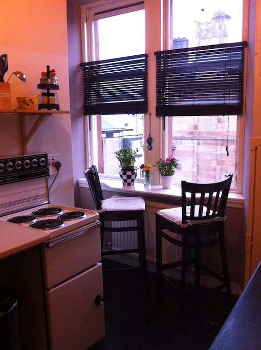 Fully equipped kitchen with electric cooker, microwave, steel sink and drying rack, fridge freezer, washing machine, breakfast bar and great street view.