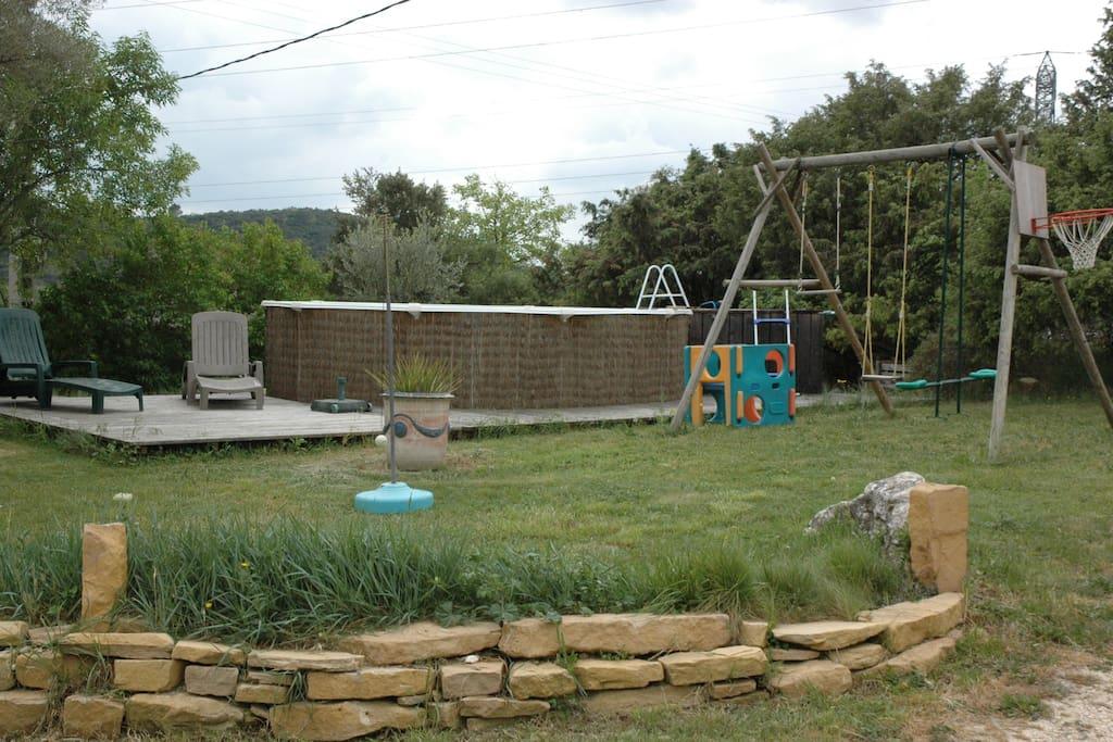 La piscine (ø4,6m x 1,2m haut), vue de la cour: terrasse bois,ponton, bains de soleil et parasol, Accès enfants sécurisé par échelle amovible.