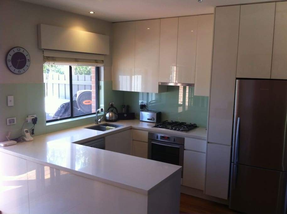 Modern kitchen with gas oven, stove and dishwahser. Adjoining utility room with washing machine and dryer and third toilet.