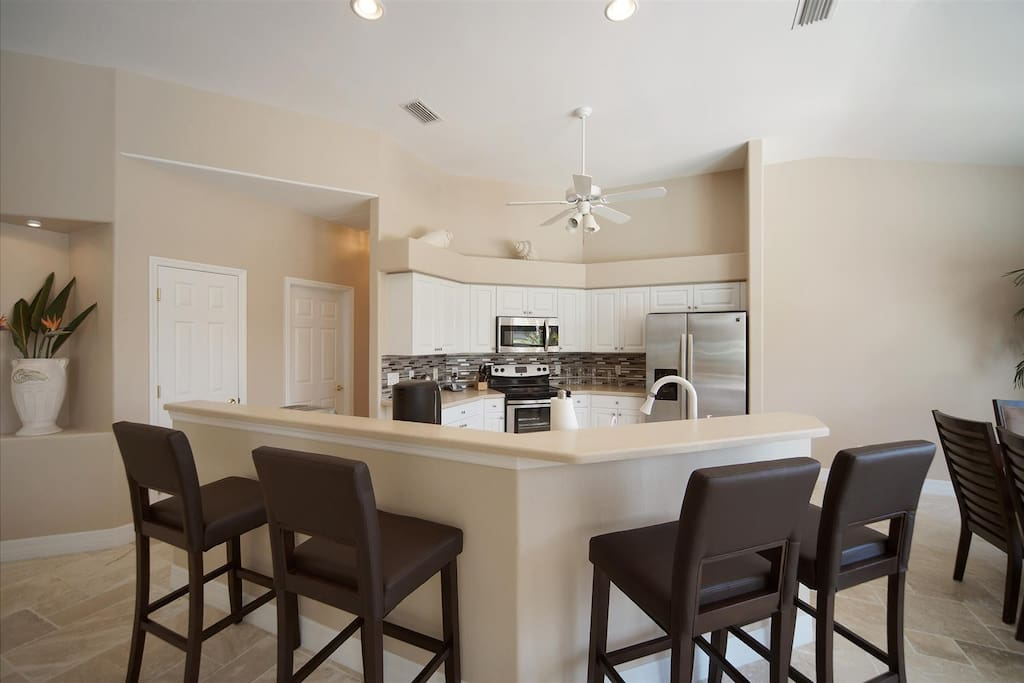 Large kitchen with stainless steel appliances and bar stools for 4 people