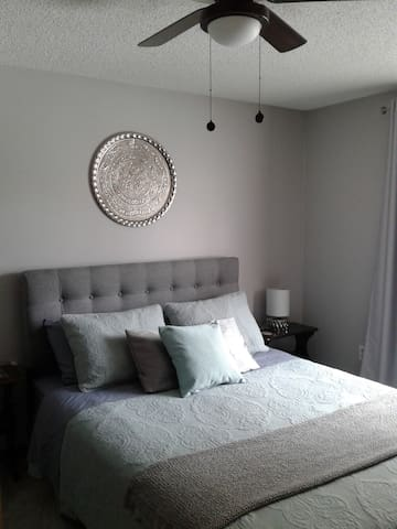 Freshly decorated bedroom with new queen size bed & linens located at the back of our home with a view of the forest lined back garden.