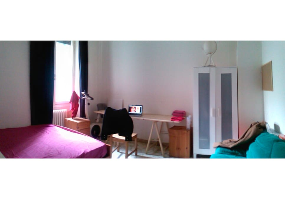 Panoramic of the room from the door, with the table, chair, etc.