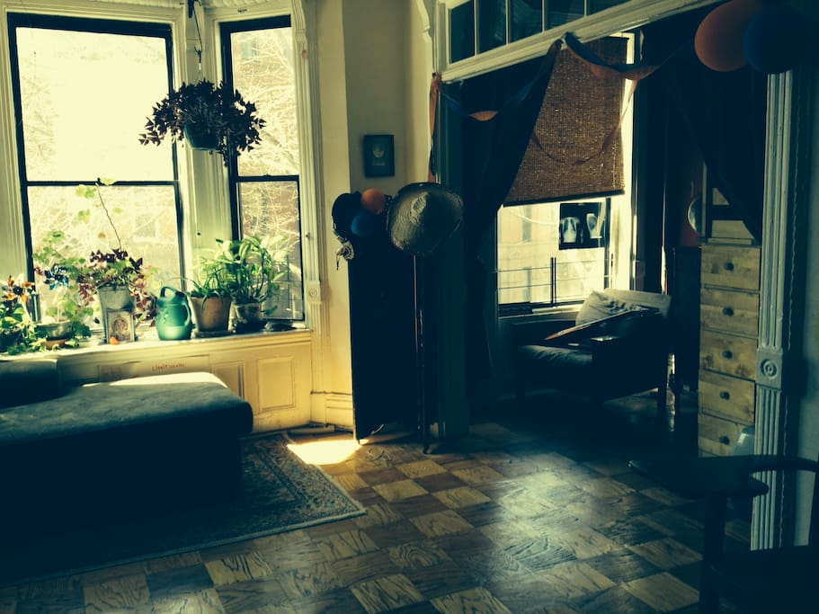 This is the front parlor, Bay window with plants and daybed. very large room connects to side bedroom which has adult sized single  loft bed .Gorgeous light floods in in the afternoon,