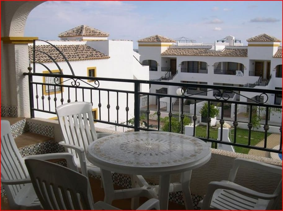 South facing balcony overlooking the pool with table & chairs.