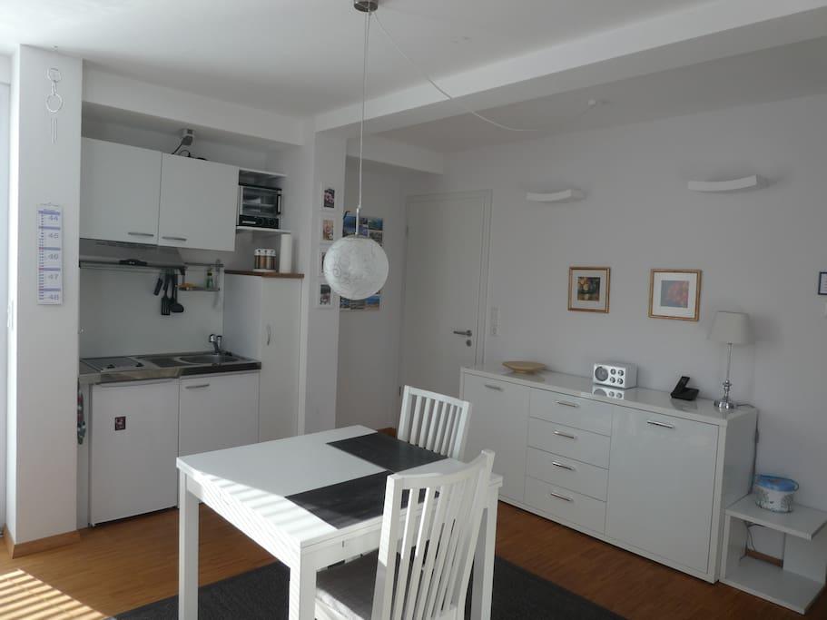 Blick auf die Singleküche mit Kühlschrank, 2 Ceran-Herdplatten und kleinem Ofen