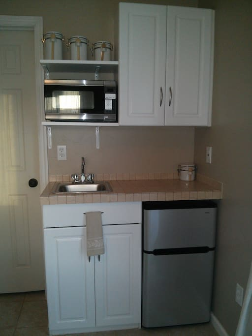 Kitchenette with cabinets, shelves, fridge/freezer, microwave, small sink, and all utensils and cleaning supplies included.