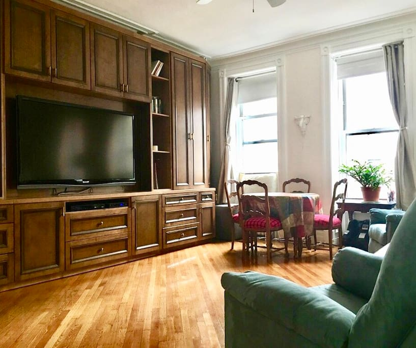"A view of the living room from the entrance.  TV is 70"" with enhanced speakers.  Dining table expands to seat 8 guests.  There is a living room coat closet and to the far left is the entrance to a full bath (shower included)."