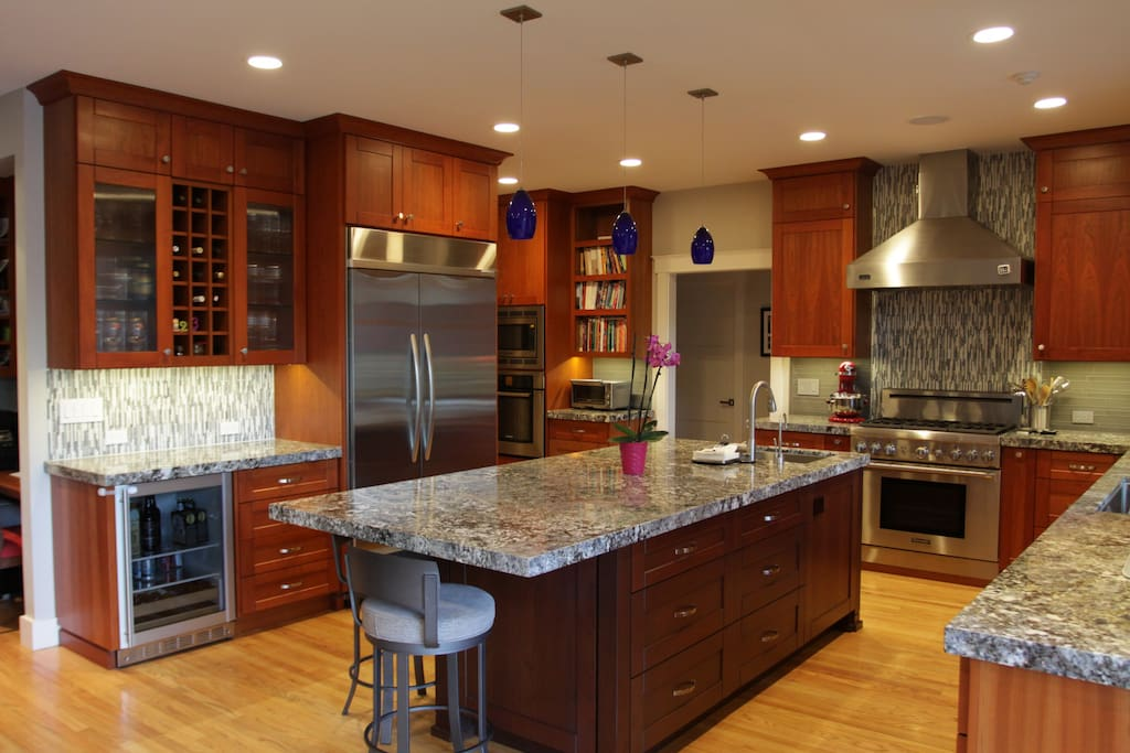 Chef's kitchen features eat-in island (seats 4), two ovens, 6 burner range, two sinks, dishwasher, microwave, and a wine fridge
