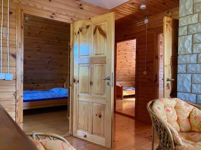 Od lewej: Sypialnia 1 z łóżkiem podwójnym Sypialnia 2 z dwoma łóżkami pojedynczymi Sypialnia 3 z dwoma łóżkami pojedynczymi. Pomiędzy sypialniami mini salonik z widokiem na pobliskie wzniesienia.