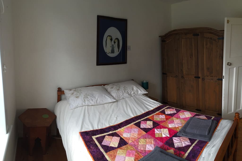 Comfortable double bed and large wardrobe with hanging space and shelves.