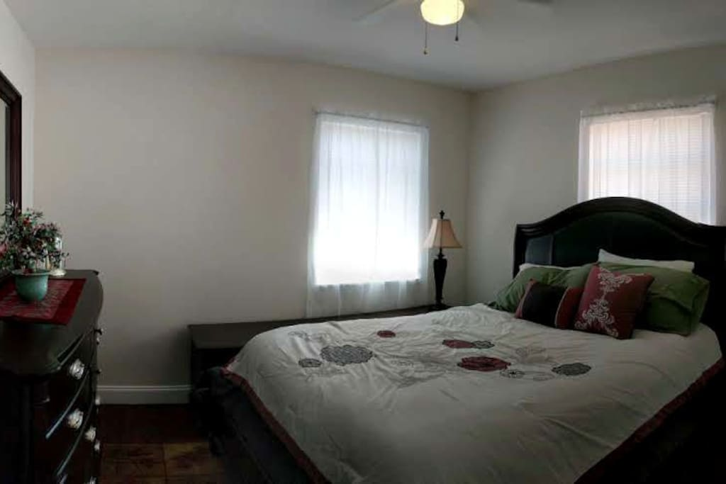The second bedroom is furnished with a queen size bed and dresser.