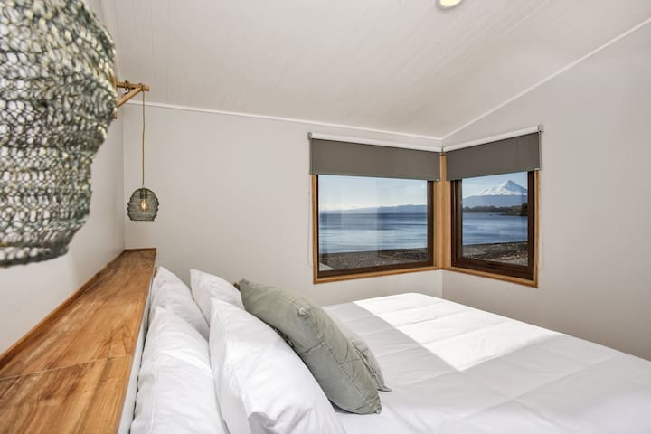 Master bedroom with a king-size bed and stunning lake and volcano views.