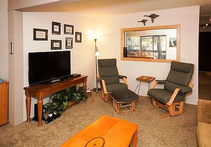 Livingroom with flat screen TV and rocking chairs. Sleeper couch is across from TV.