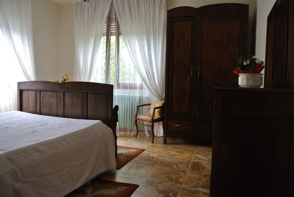 The master bedroom with its cherry-wood furniture, a plush comfortable mattress and two windows overlooking the green garden. There is also a traditional face-washing basin for your morning and evening beauty routine