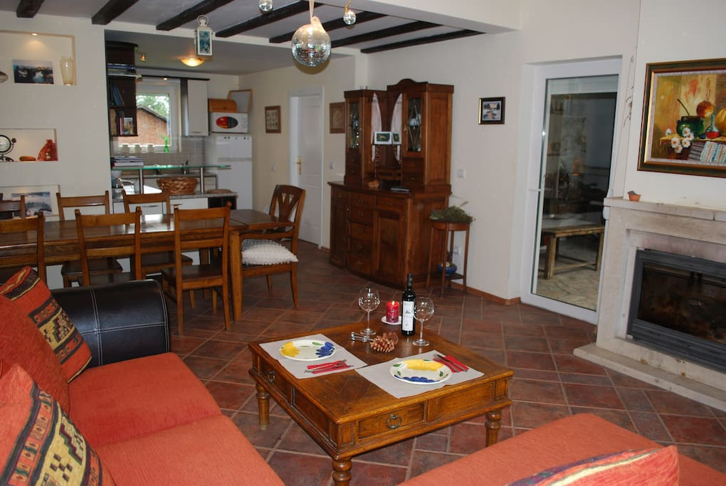Livingroom with dinning table, well equiped kitchen and exit for the garden and cover terrasse
