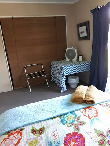 The room has everything you need a table for your personal belongings a suitcase stand a fan a bedside light and towels.