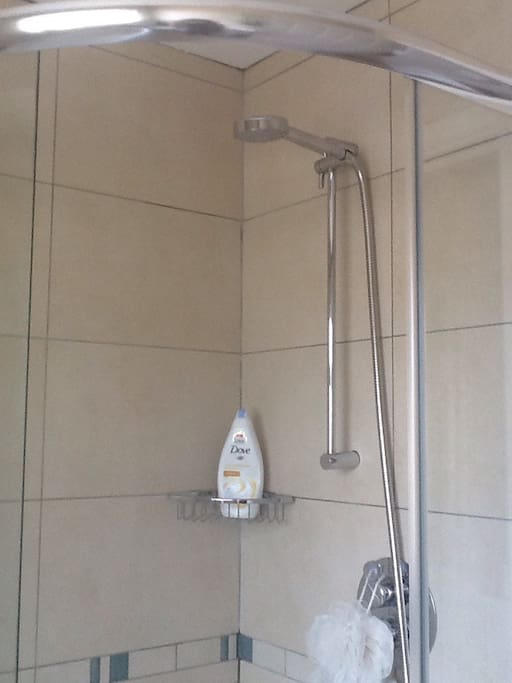 Fully tiled  bathroom with modern shower cubicle and powerful shower.