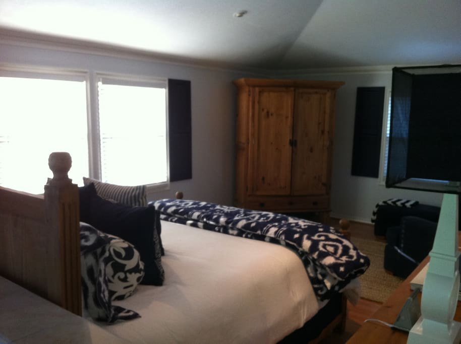 Inside Garden cottage w/ queen size bed and a large reading & nap chair, entertainment center w/ dvd player