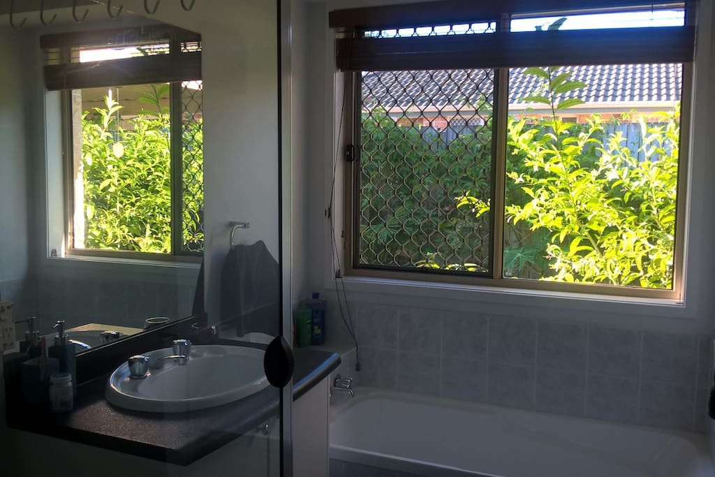 Private use guest bathroom containing a sink, a shower and a bath tub.
