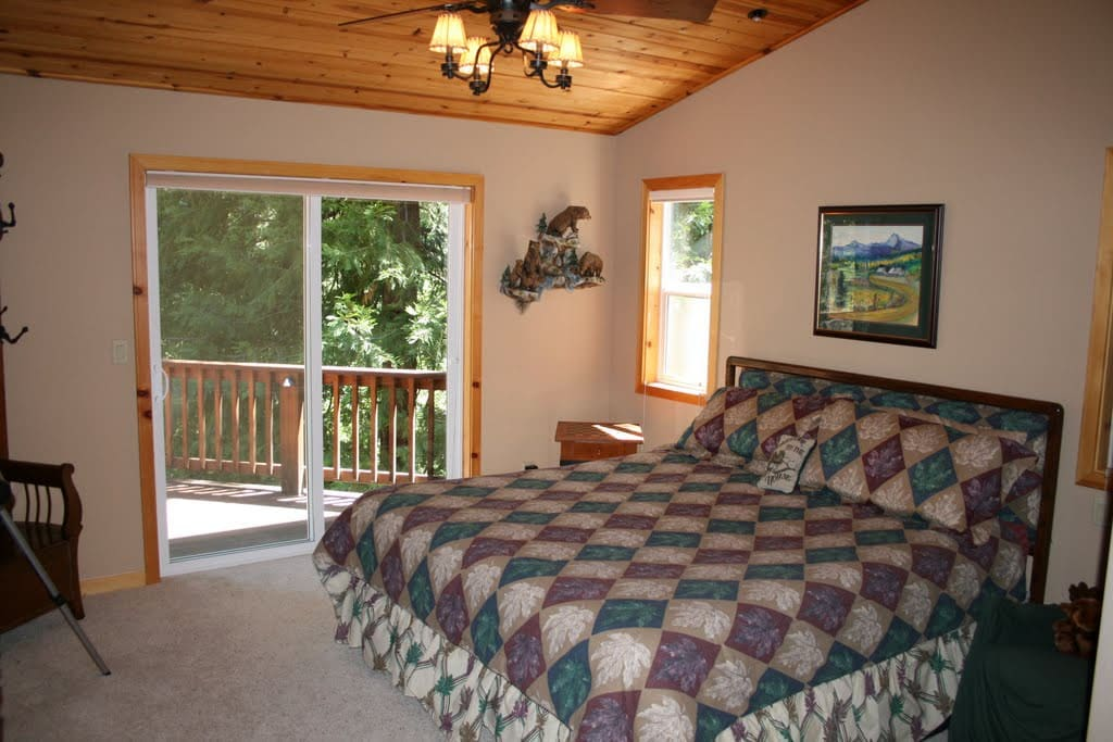 Large master bedroom with deck access and ceiling fan.