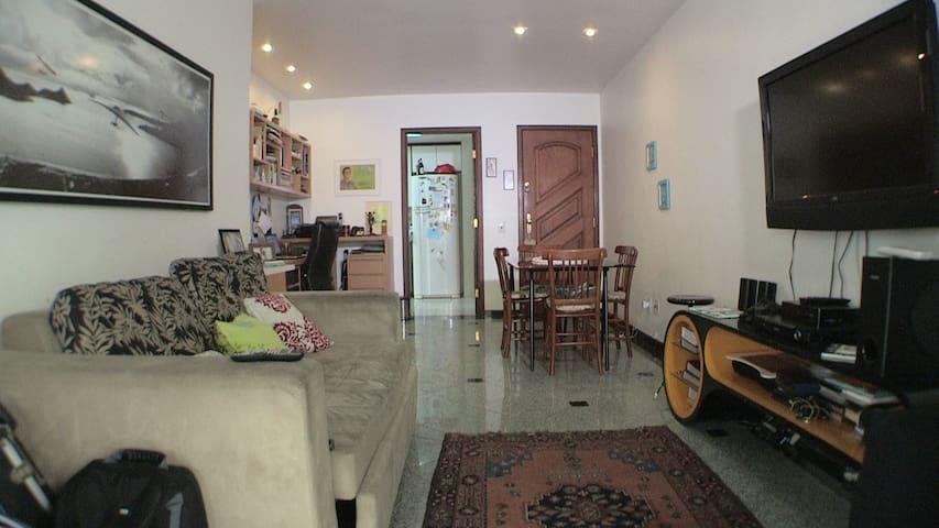 Sala de outro ângulo, cozinha espaçosa ao fundo..