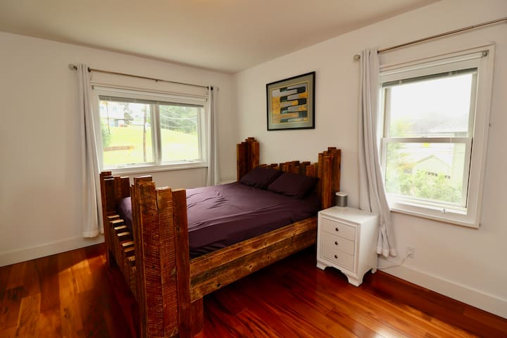 Master bedroom with queen bed I made from very locally reclaimed lumber.