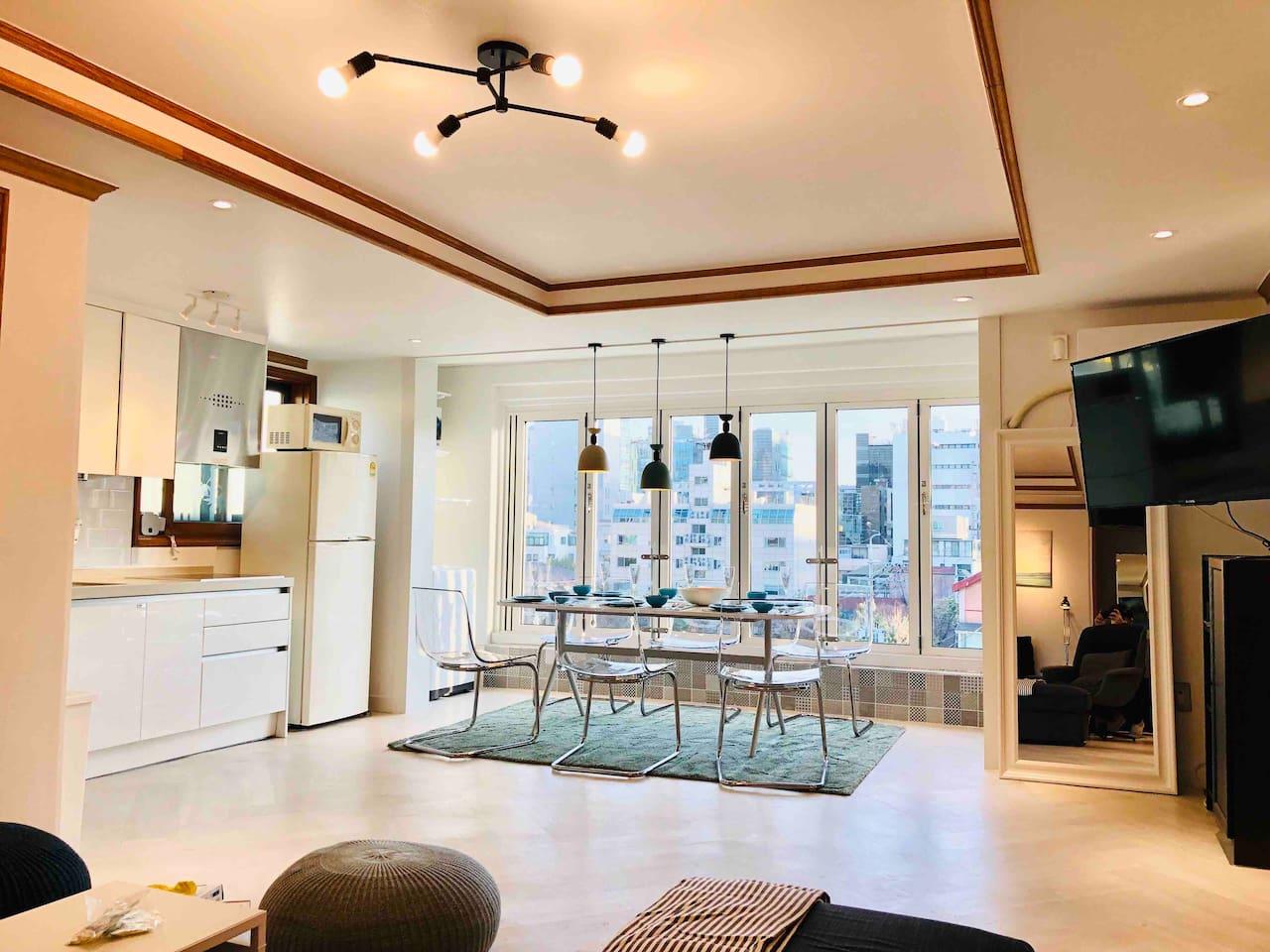 완전히 개방되는 베란다 창문 앞에 6인용 테이블이 따뜻한 Carpet 위에 놓여있어 서울 야경을 즐기며 식사를 하실수 있습니다. 거실과 주방이 Open되어 있는 구조로 여럿이서 편안히 머무실 수 있습니다.