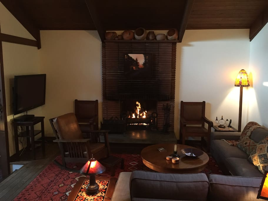 Living room has gas fireplace with remote control and TV, books, stained glass, high ceilings and objects d'art.