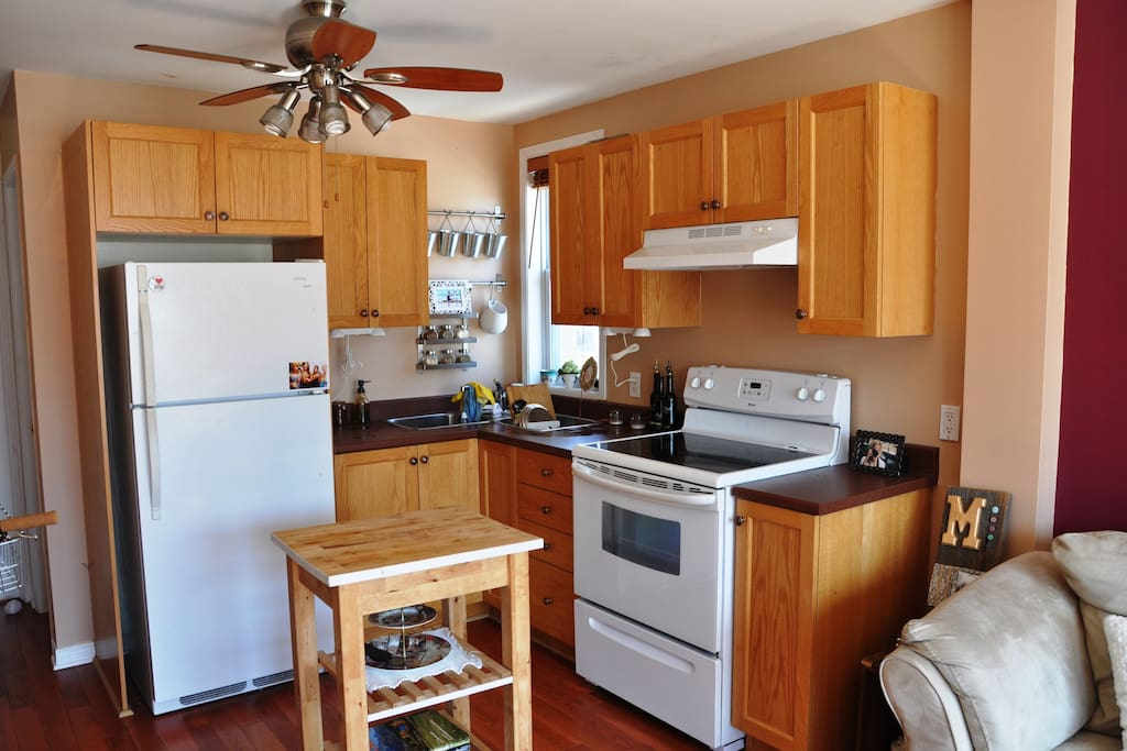Clean open concept kitchen with big fridge, clean stove, window