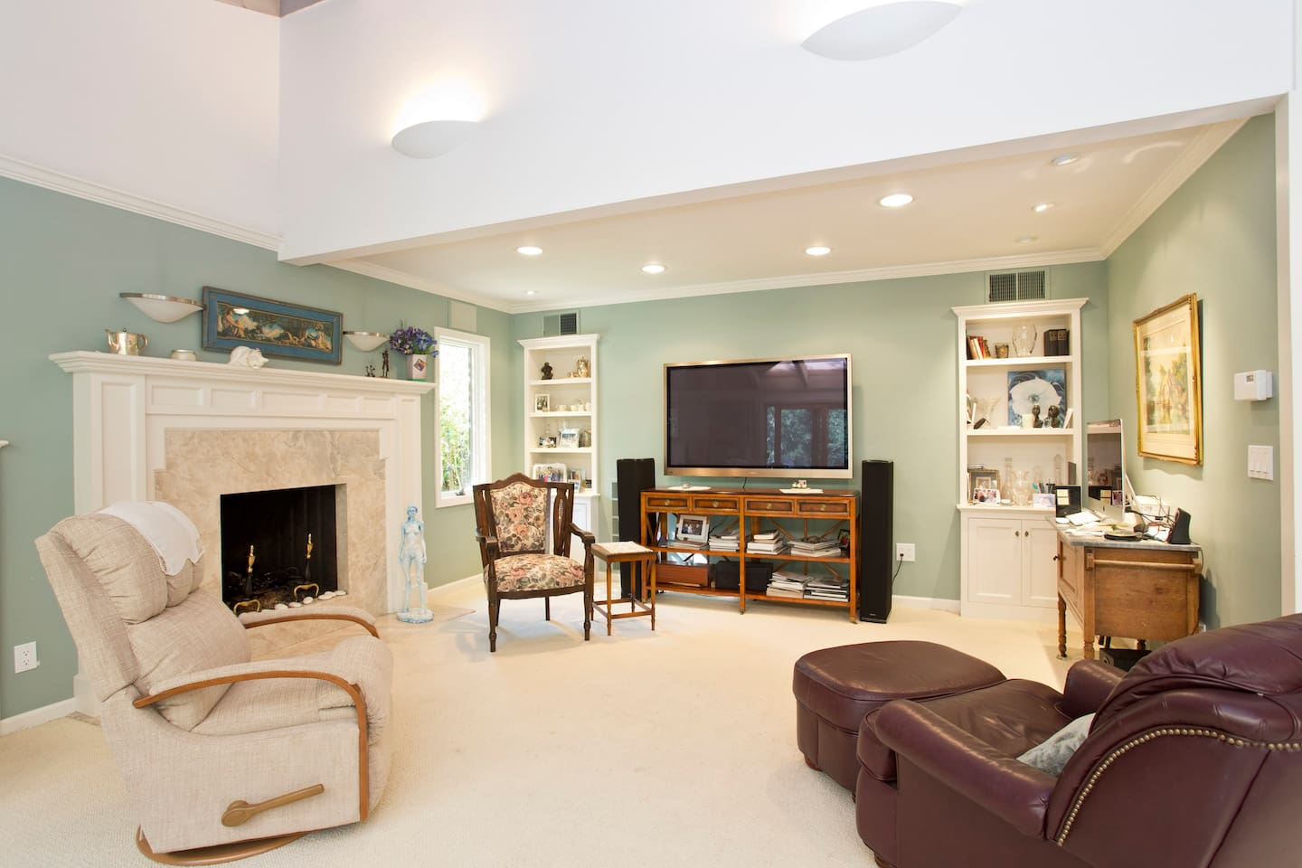 Living room with fireplace and large screen cable TV.  Room faces south so lots of sunshine