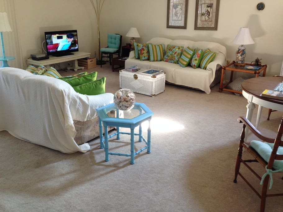 Large living room with flat screen tv and game area.