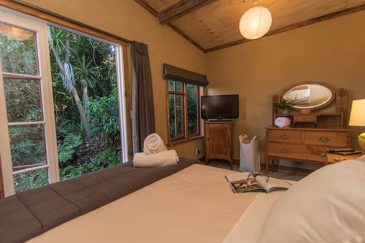 The Rainforest Master Bedroom - slip into luxurious bedding, enjoy the elegant natural furnishings,  and gaze out the window into the rainforest