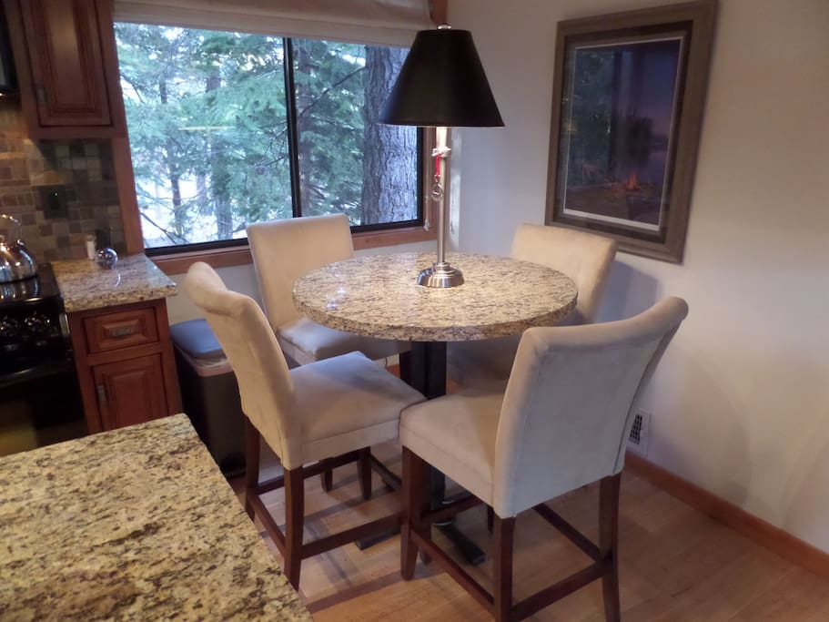 Kitchen dining area with pub height granite table seats 4 for morning coffee or intimate dining