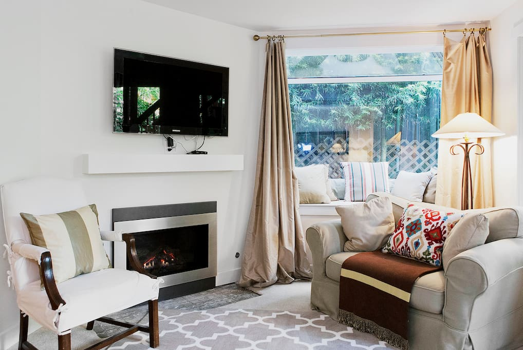 A cozy fireplace with a flat screen tv